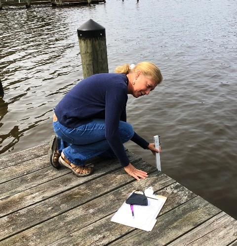 SEP Team Member Gail Cooper Measuring Water Depth at Dock